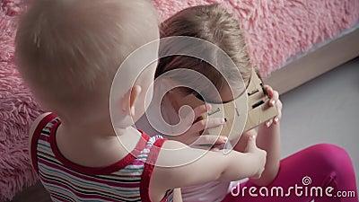 Маленькая девочка использует картон виртуальной реальности VR, прибор со что может испытать виртуальную реальность на мобильном т акции видеоматериалы