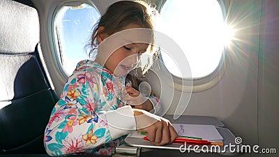 Маленькая девочка путешествуя самолетом и рисуя изображение с красочными карандашами сток-видео