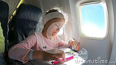 Маленькая девочка путешествуя самолетом и рисуя изображение с красочными карандашами видеоматериал
