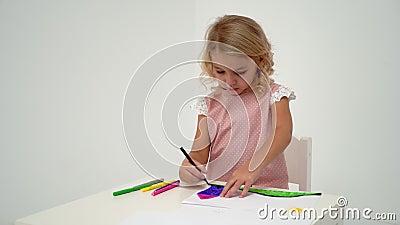 Маленькая девочка рисует за столом акции видеоматериалы