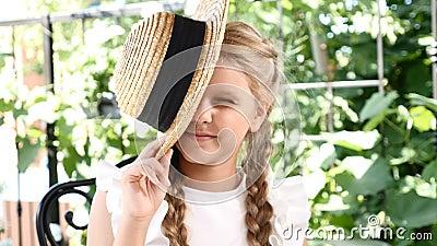 Маленькая милая девушка имеет потеху с ее соломенной шляпой подмигивая с ее одним глазом lifestyle Девушка наслаждается летним дн видеоматериал