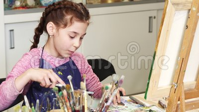 Маленькая счастливая красивая девушка усмехаясь к камере на студии искусства акции видеоматериалы