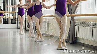 Маленькие артисти балета практикуют tendu battement во время урока в школе балета Яркие bodysuits, белое pointe видеоматериал