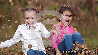 2 маленьких счастливых девушки с листьями в парке Желтое листво сток-видео