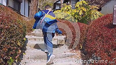 Мальчик, бежавший по лестнице в японскую горную деревню, для концепции отпуска сток-видео