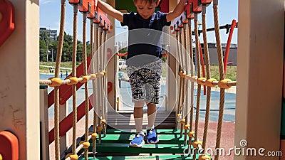 Мальчик бежит на игровую площадку в парке Счастливый ребенок катится вниз по детскому слайду Развитие дошкольного образования сток-видео