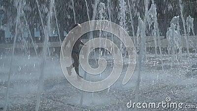 Мальчик бежит через фонтан сток-видео