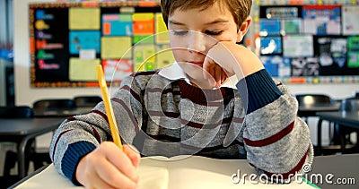 Мальчик делая домашнюю работу в классе 4k акции видеоматериалы