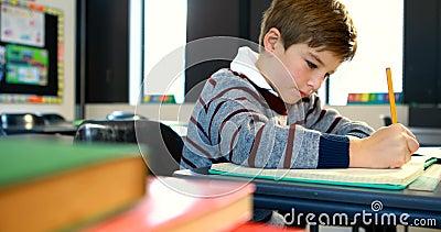 Мальчик делая домашнюю работу в классе 4k видеоматериал