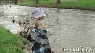 Мальчик смотрит на озеро в парке сток-видео