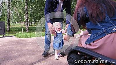 Мама и папа учат дочь шагать первыми шагами, держась за руки сток-видео