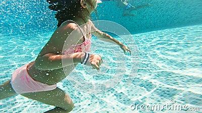 Маска маленькой девочки нося плавая под водой в бассейне сток-видео