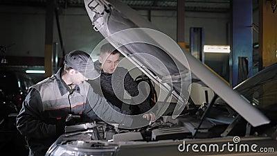 Мастер проверяет жидкости в автомобиле, переплетая крышки резервуаров, владелец автомобиля стоит близко и контролировать видеоматериал