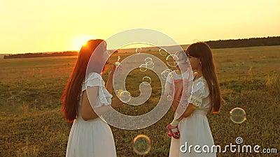Материнская мыльная мыло-пузырька улыбается счастливым детям Дочери радуются и улыбаются, пузыри летают в парке на закате солнца  акции видеоматериалы