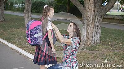Мать готовит дочь к школе Женщина выпрямляет свою форму куртки школьную форму моей дочери на улице акции видеоматериалы