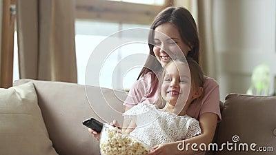 Мать держа дистанционное управление смотря ТВ с небольшой дочерью ребенк сток-видео