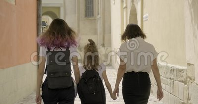 Мать и две дочери ходят вместе, на задний вид сток-видео