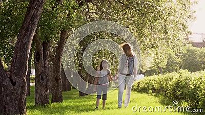 Мать идет с ее дочерью вдоль бульвара яблонь Маленькая девочка держит ее мать рукой Ребенок сток-видео