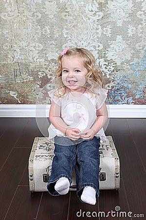 Маленькая девочка на чемодане