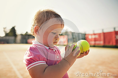 Маленькая девочка с теннисным мячом