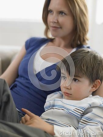 Мальчик и мать смотря ТВ дома