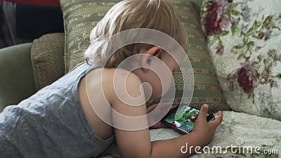 Мальчик на видео софы наблюдая на smartphone Детство прибор amuser акции видеоматериалы