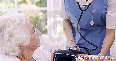 Медсестра проверяя кровопролитное давление старшей женщины видеоматериал