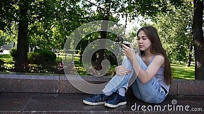 Милая девушка подростка проверяя телефон и ждать телефонный звонок сидя в парке Видео HD снимая статическую камеру сток-видео