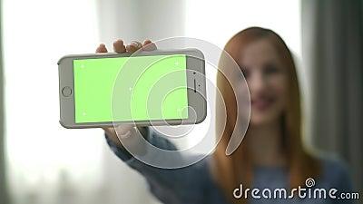Милая молодая женщина в комнате показывает что прибор с greenscreen акции видеоматериалы