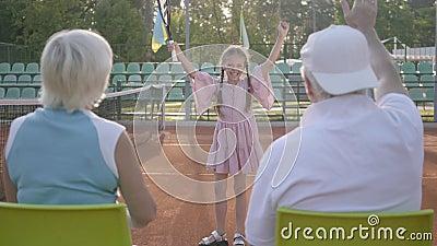 Милая смешная девушка с 2 отрезками провода выиграла теннисный турнир Ее деды сидя близко с их задними частями к камере видеоматериал