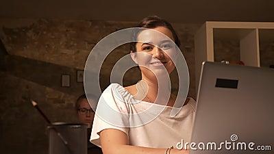 Милая улыбка кавказской женщины сидя и смотря ее компьтер-книжка, работая в офисе кирпича с сподвижницей позади видеоматериал