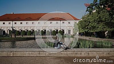 Миленькая девушка с рюкзаком, сидящая на парапете пруда есть дворец валленштейна и пруд с рыбой и рыбой. видеоматериал