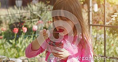 Миленькая 6-7-летняя девочка ест фруктовое десерт-желе в летнем саду Медленное видео акции видеоматериалы