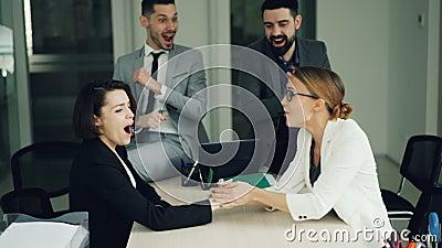 Милые молодые женщины состязаются в армрестлинге в офисе во время перерыва пока парни наблюдают и смеются корпоративно видеоматериал