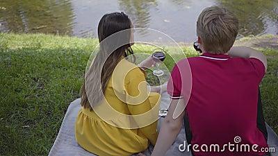 Милые молодые счастливые пары в любов делая пикник с вином в красивых зацветая саде или парке жизнерадостно беседуя и видеоматериал