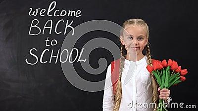 Милый усмехаясь пук удерживания девушки тюльпанов около доски приветствует назад в школу видеоматериал