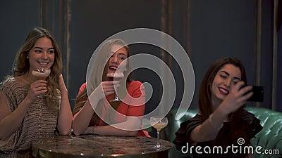 3 милых девушки сидят в кафе или ресторане красиво представляя и принимая selfie фото для социальных сетей акции видеоматериалы