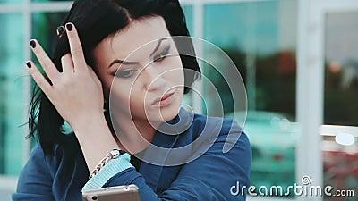 Милая девушка делая selfies на smartphone Молодая женщина брюнет с мобильным телефоном Устройства и люди Smartphone внутри акции видеоматериалы