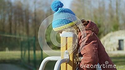 Милая маленькая девочка в голубой шляпе играя на спортивной площадке Женщина поворачивая дальше carousel и усмехаться Беспечально сток-видео