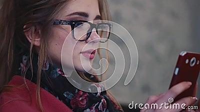 Милая молодая женщина отправляя СМС сообщение с ее телефоном Естественная красота, был онлайн Социальные сети, facebook Экран акции видеоматериалы