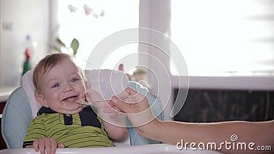 Милая усмехаясь еда младенца, сидя на месте младенца дома Будьте матерью подавать ее прелестное одно годовалое с ложкой видеоматериал