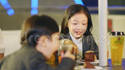 Младший азиатский брат и сестра едят десерт сток-видео