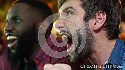 Многонациональные мужские вентиляторы радуясь любимая победа команды спорта в пабе, игре напряжения видеоматериал