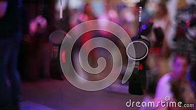 Много наушников висят на проводе на под открытым небом партии фестиваля зрелищность вечер праздники сток-видео