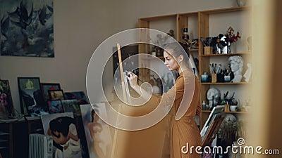 Молодая дама сфокусирована на картине работая в современной студии наслаждаясь творческим хобби Подлинные художественные произвед видеоматериал