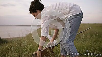 Молодая девушка брюнет в белых рубашке и джинсах на meado около озера Девушка подготавливает мольберт для работы акции видеоматериалы