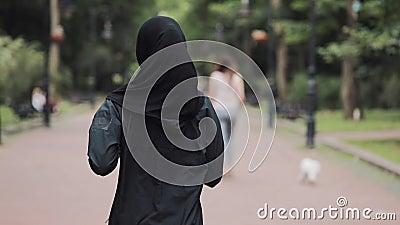 Молодая молодая молодая девушка из группы 'Прэсти', носящая хиджабт, бегающая в парке на заднем плане, понимает концепцию здорово видеоматериал
