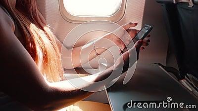 Молодая женщина использует smartphone во время полета самолета видеоматериал
