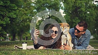 Молодая женщина принимает selfie в парке лежа на траве с ее парнем и собака, прелестное животное чихает и акции видеоматериалы