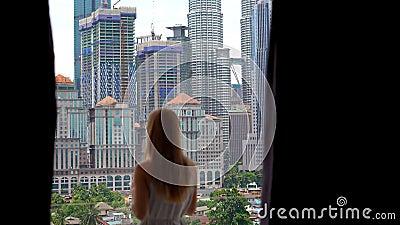 Молодая женщина приходит к балкону ее квартиры с взглядом в центре города вполне skyscrappers и выпивает утро акции видеоматериалы